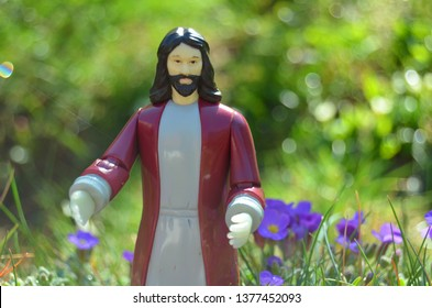 Jesus Christ action figure toy in a garden, surounded by violet lobelia flowers