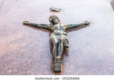 Jesus christ bronze sculpture over cross at tomb at cemetery in Brazil