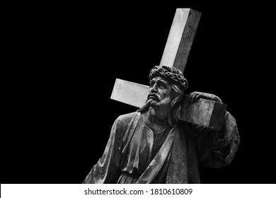 Jesus Christ with cross.  Ancient statue isolated on black background.