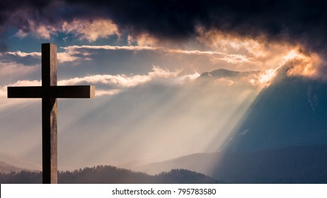 Jesus Christ cross. Easter, resurrection concept. Christian wooden cross on a background with dramatic lighting, colorful mountain sunset, dark clouds and sky, sunbeams