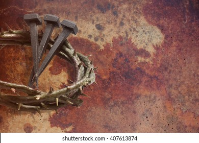 Jesus Christ crown of thorns and nails on a grunge background. Focus is on part of the nails.