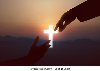 Jesus Christ giving a helping hand to human with a sunset sky background