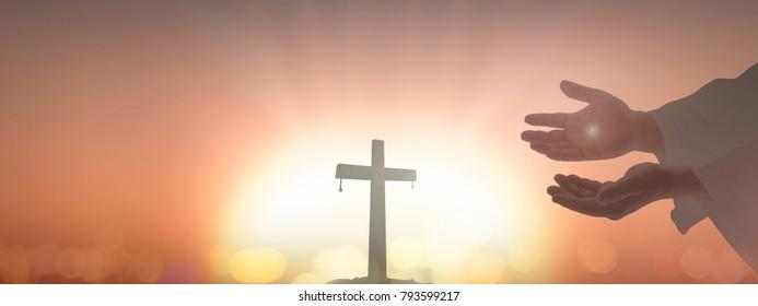 Jesus Christ hands showing scars over blurred cross sunset background.