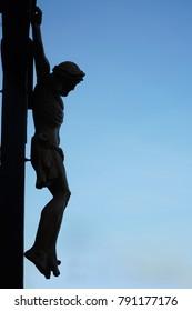 Jesus Christ hang on the cross against blue sky and european catholic church.