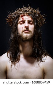 Jesus Christ of Nazareth with crown of thorns prays with raised head. Closeup portrait