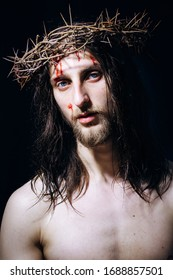 Jesus Christ of Nazareth with crown of thorns looks at people. Closeup portrait