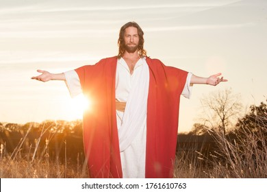 Jesus Christ with outstretched arms in welcoming blessing at sunset wearing beautiful red & white robe