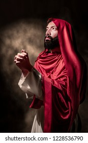 Jesus christ praying to god with hand gesture over black background