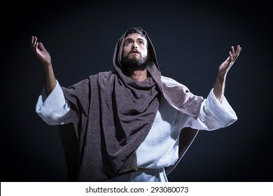 Jesus Christ praying to God with open arms in the dark blue night