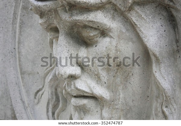 Jesus Christ statue against a background of gray stone