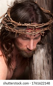 Jesus Christ wearing a crown of thorns and carrying the cross for mankind's sins in artistic mystical portrait