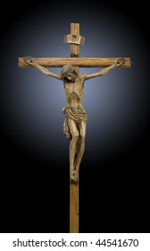 Jesus crucified on the cross, a wooden statue on black background