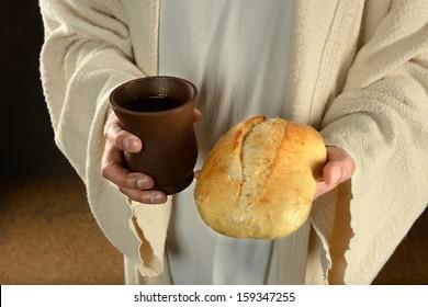 Jesus hands holding bread and wine over dark background