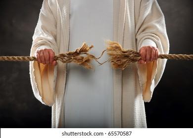 Jesus hands holding frayed rope over dark background