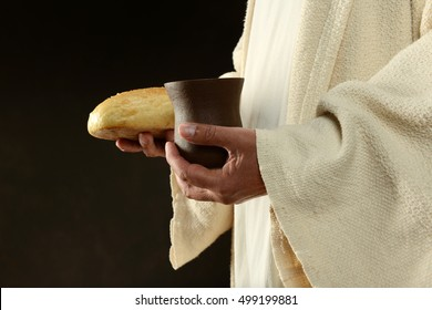 Jesus hands holding the wine and bread against a dark background