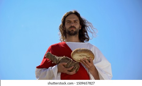 Jesus holding bread and bottle of wine, sharing sacramental meal, Holy Eucharist