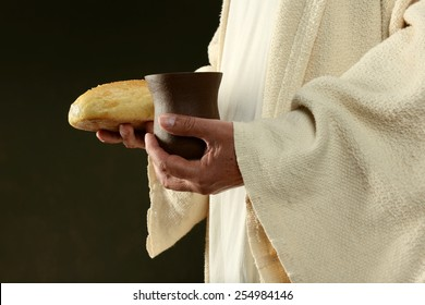 Jesus holding bread and a cup of wine isolated on a dark background