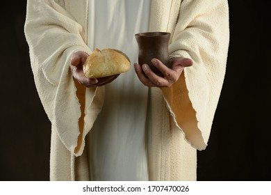 Jesus holding and offering the bread and a cup of wine against a dark background