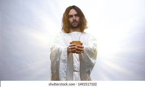 Jesus holding wine on illuminated background, Eucharist in Catholic church