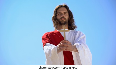 Jesus holding wooden cross against blue sky, conversion to Christianity, baptism