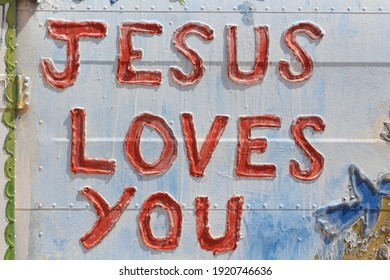 Jesus loves you written on old car door
