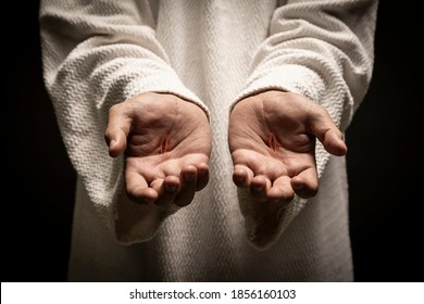 Jesus of Nazareth showing the wounds on his hands while praying on a dark night after being resurrected.