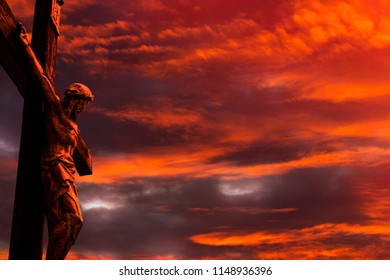 Jesus on a cross against burning red sunset sky with clouds and little patches of light coming through