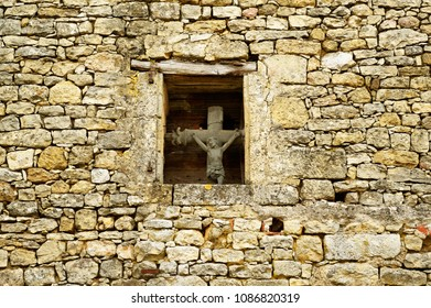 Jesus on cross, ancient crucifix, visible from outside, placed in small window in the middle of medieval facade. Dordogne, southwest of France.