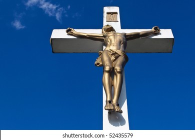 Jesus on the cross in front of a blue sky background.