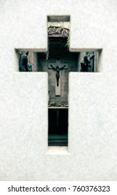 Jesus on a cross on a tomb's wall, as seen through a cross shaped window.
