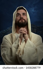 Jesus praying at night with hands clenched with nocturnal landscape in background