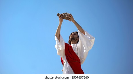 Jesus raising wine in hands to sky, blessing sacramental Eucharist beverage