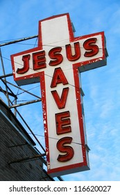 """Jesus Saves. Old """"Jesus Saves"""" neon sign off the side of an old building in Toronto, Canada."""