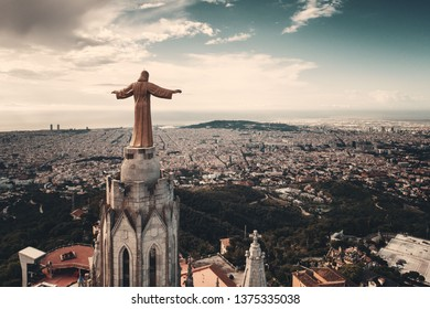 Jesus statue atop of Tibidabo Temple of the Sacred Heart of Jesus viewed from air in Barcelona, Spain
