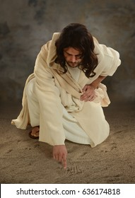 Jesus using his finger to white in the sand