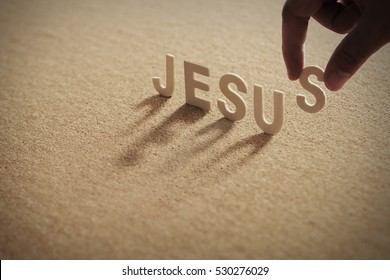 JESUS wood word on compressed board with human's finger at S letter