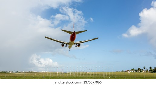 Jet aeroplane in blue sky coming in to land at an airport