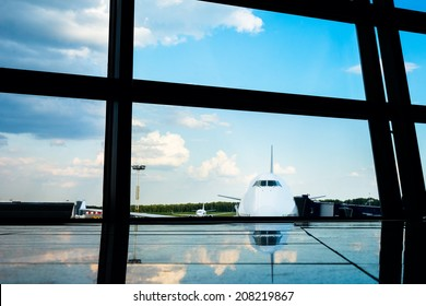 Jet aircraft behind airport windows. With reflection on the floor.