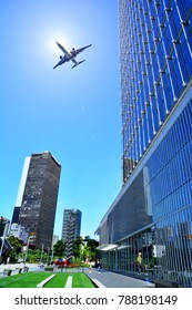 Jet aircraft flying to a background of blue sky of the city