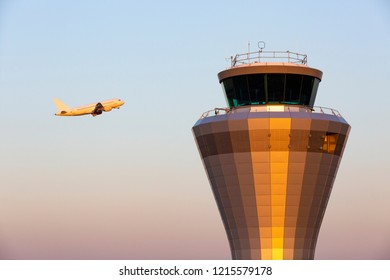 A jet aircraft flying past an air traffic control tower as it takes of at Birmingham Airport in England, UK