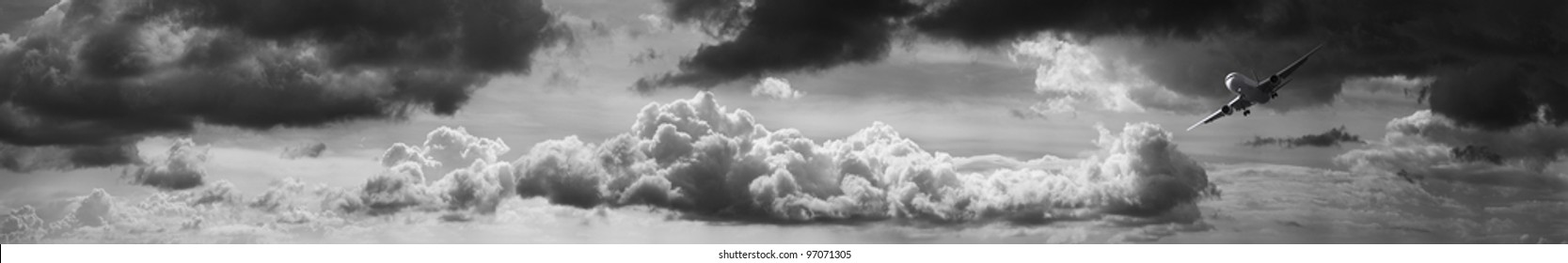 Jet aircraft in a stormy sky. Panoramic composition in very high resolution. Monochrome image.