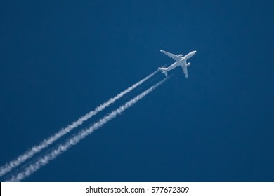 Jet airliner flying high in the sky leaves contrails in the clear blue sky