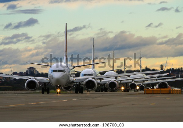 jet airliners lined up at dusk on runway