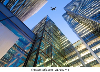 A jet airplane silhouette with business office building towers in London