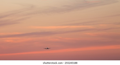 jet airplane in silhouette landing off at sunset