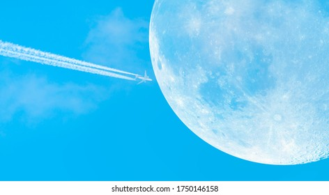 """Jet airplane with trail of fuel on blue sky on the backgroun full moon """"Elements of this image furnished by NASA"""""""