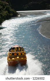 A jet boat driving up the Waimakariri River in New Zealand shot from a helicopter.