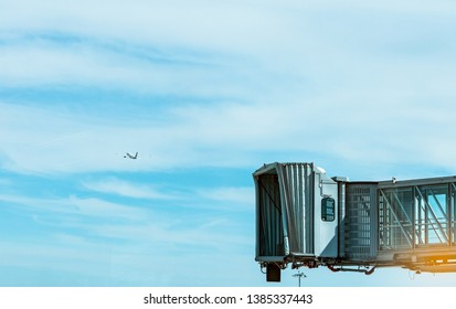 Jet bridge after commercial airline take off at the airport and the plane flying in the blue sky and white clouds. Aircraft passenger boarding bridge docked. Departure flight of international airline.