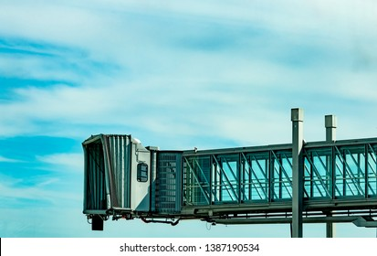 Jet bridge after commercial airline take off at the airport against blue sky and white clouds. Aircraft passenger boarding bridge docked. Departure flight of international airline. Empty jet bridge.