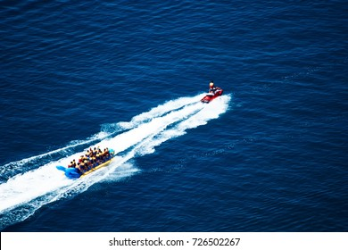 The jet carries a people in life jackets on the banana boat on the blue sea. The view from the top.
